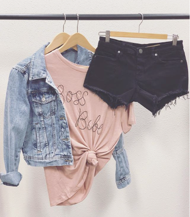 M.Marie jacket, graphic tee, and shorts hanging on a rack